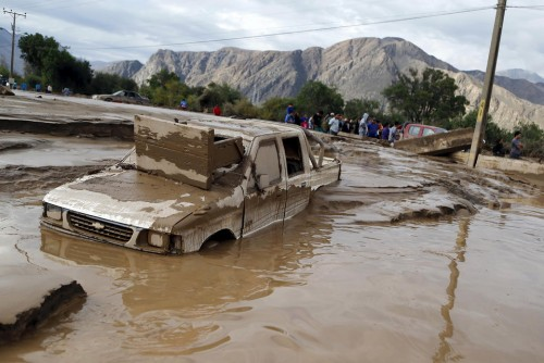 A damaged car covered in mud lies on a street at Copiapo city