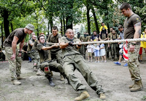 epa04883268 Ukrainian recruits compete in a tug-of-war during a competition at the Azov Battalion base, in Kiev, Ukraine, 14 August 2015. About 40 Ukrainian recruits took part in a competition for a chance to serve in the all-volunteer Azov Battalion and to be send to the eastern Ukrainian conflict zone. The Ukrainian military and pro-Russian separatists on 13 August have exchanged heavy artillery fire despite a ceasefire that banned such weapons from the front lines, the Organization for Security and Cooperation in Europe (OSCE) said. The Ukrainian government pointed to the heaviest combat since a ceasefire was agreed in February, and said two people had been killed and 10 wounded in the last 24 hours as some 153 artillery rounds were fired at Ukrainian positions. The rebels alleged that civilians were killed in fighting near Donetsk, a separatist stronghold. The Azov Battalion is a military volunteer unit within the Ukrainian National Guard. The unit is said to be ultra-nationalist, extreme right-wing orientated and even labelled neo-Nazi.  EPA/ROMAN PILIPEY