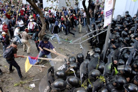 Protesters clash with police near the government palace in Quito, Ecuador, Thursday, Aug. 13, 2015. A strike by a broad coalition upset with President Rafael Correa virtually paralyzed the capital, provincial cities and stretches of the Panamerican highway. The protesters are indigenous activists, unionists, environmentalists and members of the traditional political opposition. (AP Photo/Franklin Jacome)