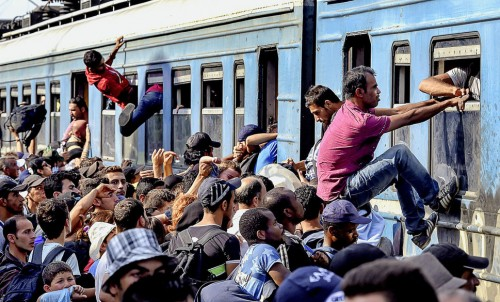 epa04882347 Migrants fight to get onto the train heading to the Serbian border at the train station in Gevgelija, The Former Yugoslav Republic of Macedonia, 13 August 2015. From the beginning of the year to mid-June 2015, nearly 160,000 migrants landed in the southern European countries, mainly Greece and Italy, on their way to countries in Western and Northern Europe, according to estimates by the International Organization for Migration (IOM).  EPA/GEORGI LICOVSKI